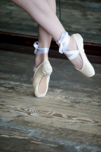 Close-up shot of female feet in ballet shoes dancing on the wooden floor